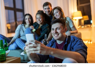 friendship, technology and entertainment concept - happy friends with smartphone, snacks and non-alcoholic drinks hanging out at home in evening