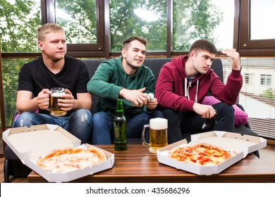 friendship, technology, games and home concept - smiling male friends playing video games, drink beer and have fun at home