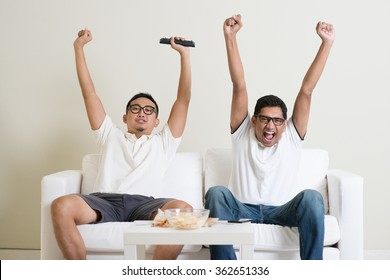 Friendship, technology and home concept. Happy male friends with remote control and junk food at home.