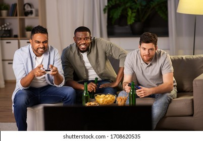 friendship, technology and leisure concept - smiling male friends with gamepads and beer playing video game at home at night