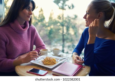 Friendship and technology two pretty girls using smartphones while drinking tea or coffee at cafe. Young women colleagues dressed in casual outfit wear having conversation during work break.