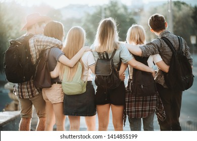 Friendship, togetherness, traveling, vacation, holidays, togetherness, sightseeing, city tour, student exchange program. Young people with backpacks standing close hugging admiring the city view