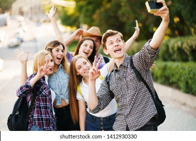 Friendship, togetherness, youth, holidays. Group of friends taking selfie at camera in city