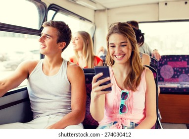 friendship, travel, summer vacation, technology and people concept - smiling couple with smartphone traveling by tour bus and making selfie