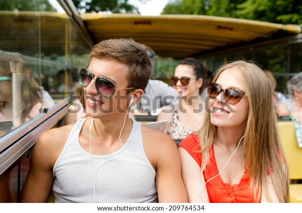 friendship, travel, vacation, summer and people concept - smiling couple with earphones traveling by tour bus