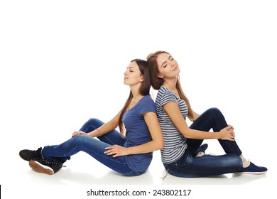 Friendship. Two smiling young girls friends sitting on the white studio floor back to back, with closed eyes, relaxing enjoying, isolated on white background.