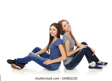 Friendship. Two smiling young girls friends sitting on the white studio floor back to back, isolated on white background.Full length females sitting on a floor and laughing.