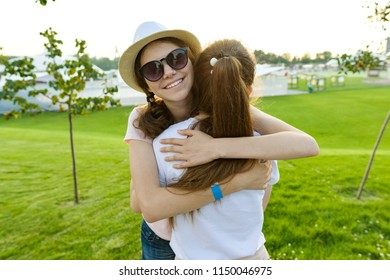 The friendship of two teenage girls, best girlfriends have fun in nature, on the green lawn of recreation park and entertainment. Embrace the greeting and parting
