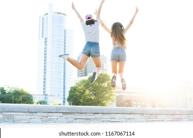 Friendship. Two young happy hipster girls having fun, smiling, laughing, jumping, walking outdoor on the street, summer relax concept
