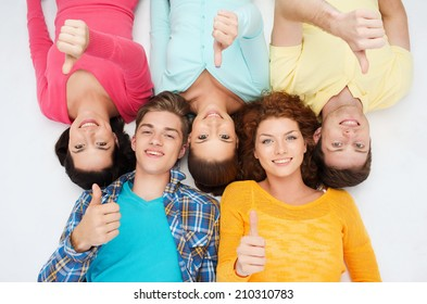 friendship, youth, gesture and people - group of smiling teenagers lying on floor and showing thumbs up