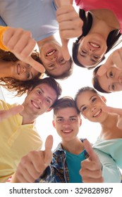 friendship, youth, gesture and people - group of smiling teenagers in a circle showing thumbs up