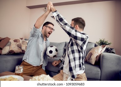 Friendship,sport,people and entertainment concept-happy male friends watching soccer on tv at home.