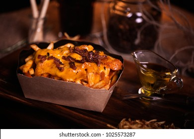 Fries food photo. Street food. Unhealthy tasty grilled french fries with cheese and bacon in homemade craft box. Closeup with unfocused background. Rustic color style.