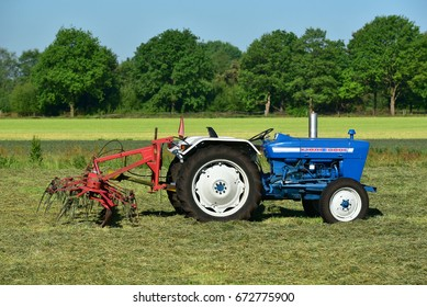 FRIESLAND, NETHERLANDS - MAY 26, 2017: Blue Ford 3000 Series Farm Tractor and rotary rake. The Ford 3000 is a tractor that was introduced by Ford in the spring of 1965.