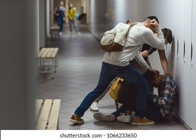 frightened african american schoolboy being bullied in school corridor