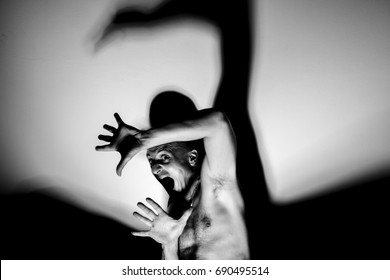 Frightened and alarmed man, very afraid fugitive, terrified and trapped clandestine man in full light with big shadow, protecting himself with his hands, nightmare scene