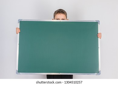 Frightened boy holding a message board, hiding behind her so that only his eyes and the tips of his ears are visible