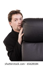 Frightened businessman hiding behind a chair