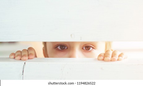Frightened child is spying through a wooden fence. Scared child boy. Human emotion, facial expression. Sad kid outdoors. Bored little boy