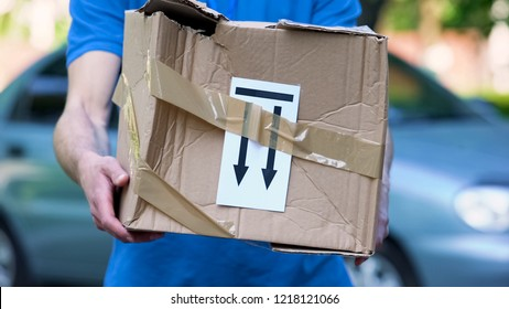Frightened delivery worker giving broken customer parcel, shipment accident