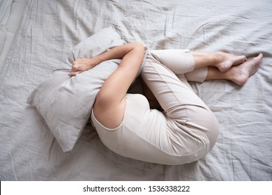 Frightened depressed middle aged woman lying alone on bed in fetal position covering head with pillow feeling afraid or depressed suffer from insomnia mental problem abuse violence concept, top view