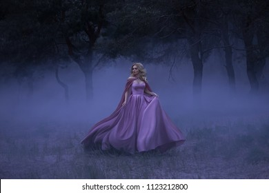 A frightened girl blonde runs away from a forest that has covered a thick fog. On the elf, a luxurious purple dress with a long train and a raincoat. Artistic photo.