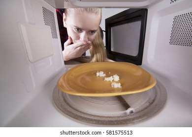 Frightened girl looking in microwave. Crumbs white bread on plate isolated in oven. Concept of poverty. The studio on white background