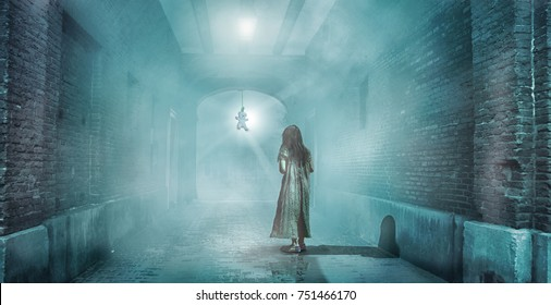 A frightened girl is standing in dark and misty tunnel staring at a teddy bear hanging on a rope