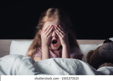 frightened kid screaming and covering eyes with hands while sitting on bedding near teddy bear isolated on black