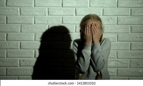 Frightened little girl closing eyes with hands, witness of family violence