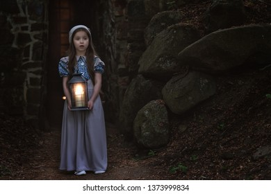 Frightened little girl in retro-style clothes is standing with a lantern near the fortress wall.