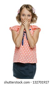 Frightened little girl standing with hands over mouth, over white background