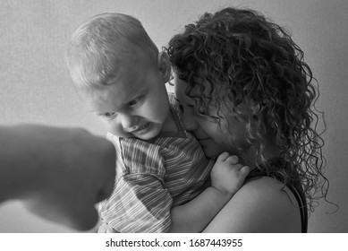 Frightened mother hugs the child in focus, father's fist out of focus, the theme of domestic violence, black and white photo.