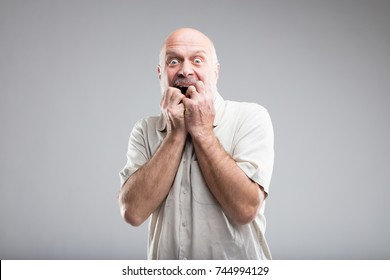 frightened old man in an exaggerated expressino of fear - studio portrait on neutral background