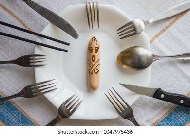 A frightened sausage is on the plate, there are a lot of forks around. Greedy contenders, the coveted prize. A table, a light tablecloth. View from above.