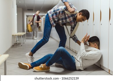 frightened schoolboy being bullied by classmate in school corridor under lockers while other boy running to help him