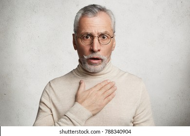 Frightened shocked bearded man has beard stares at camera with bated breath, hears shocking news, can`t believe in them, isolated over white concrete background. People, pension, reaction concept