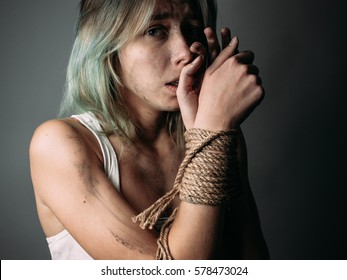 Frightened woman with bound hands on gray background.