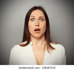 frightened woman looking at camera over dark background