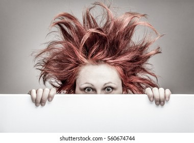 Frightened woman with messy hair hiding