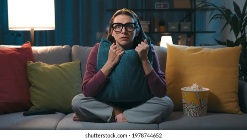 Frightened woman sitting on the couch and watching a horror movie on TV, she is hugging a pillow