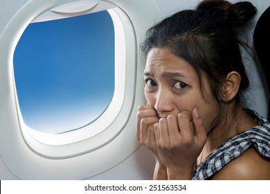 frightened woman sitting at the window of the plane. Portrait of a frightened woman at the window in a flying aircraft. Frustration and stress of flying plane. Fear of passenger plane crash accident.