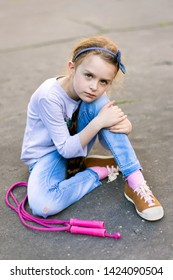 Frightened youg girl sitting on the pavement with skipping rope looking towards camera