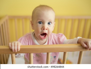Frightened young baby in crib