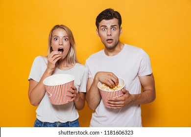Frightened young couple standing isolated over background, eating popcorn