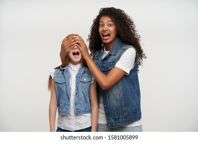 Frightened young dark haired curly woman rouning eyes and looking fearfully to camera with wide mouth opened, closing eyes of redhead little girl with palms, isolated over white background