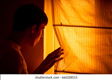 Frightened young man stands beside window and cautiously pushes curtain to one side to look out