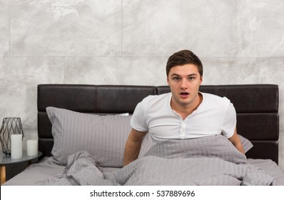 Frightened young man woke up from a nightmare sitting in stylish bed with grey colors and near bedside table with candles in a bedroom in loft style