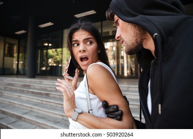 Frightened young woman with mobile phone shouting and being attacked by criminal man on the street