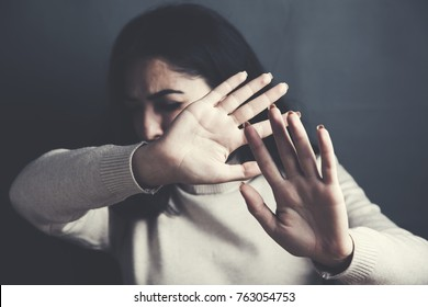 Frightened young woman on dark background